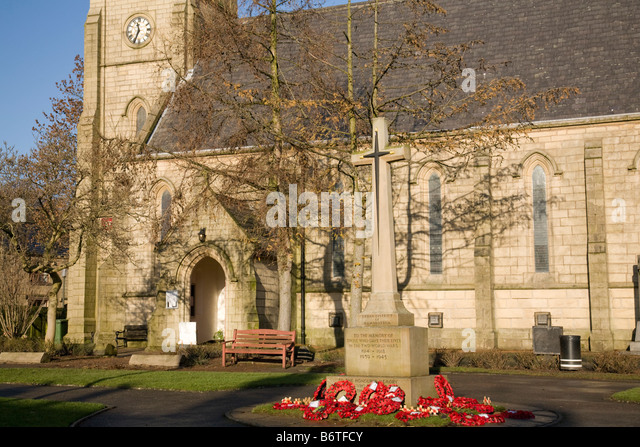 poppies surround a war memorial at st paul church of england crow lane ramsbottom - Stock Image