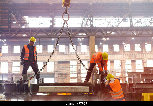 Steel workers fastening crane chain in factory - Stock Image