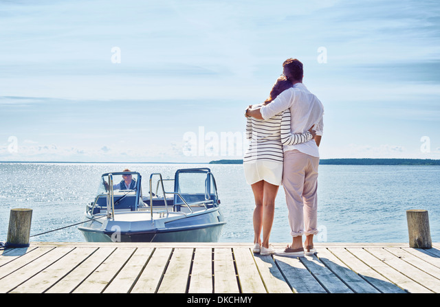 Young couple on pier looking at view, Gavle, Sweden - Stock Image