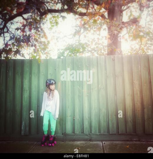 Girl wearing rollerskates leaning against fence - Stock Image