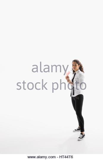 Portrait confident businesswoman holding paper airplane against white background - Stock-Bilder