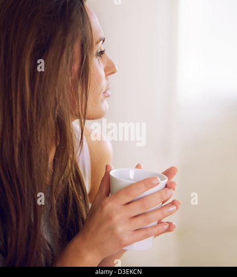Closeup of an attractive woman eating a healthy breakfast - Stock Image
