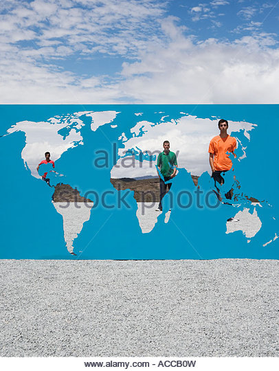 Three men standing behind world map outdoors - Stock Image