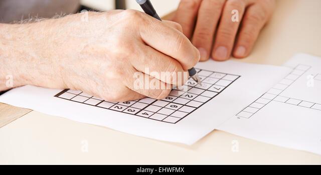 Hand of senior man solving sudoku quiz with a pen - Stock-Bilder