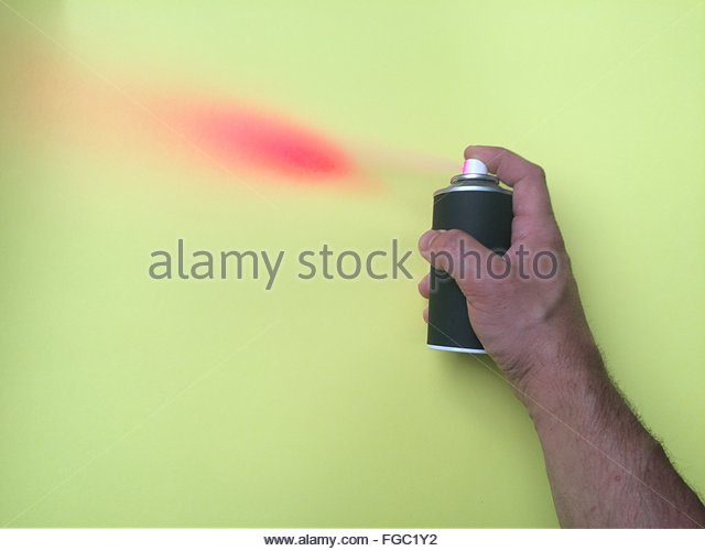 Cropped Hand Of Man Spray Painting On Yellow Wall - Stock Image