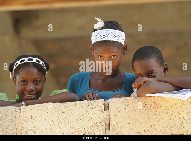 Three young black children leaning on a wall. - Stock Image