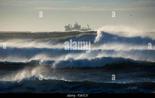 waves breaking around a trawler off the Reykjanes Peninsula, Iceland - Stock Image