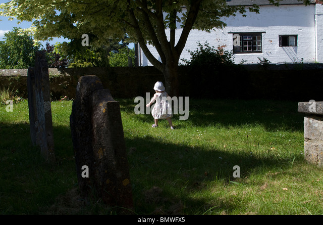 young girl running around tombs and playing in a Graveyard,Chudleigh in Devon,High Street, Chudleigh, Devon, England, - Stock Image