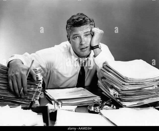 1950s PORTRAIT MAN OVERWORKED WITH DESK FULL OF PAPERS - Stock Image