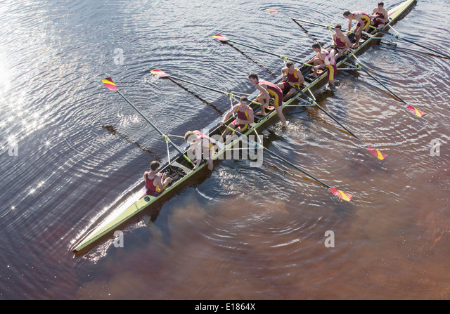 Rowing team in scull on lake - Stock Image