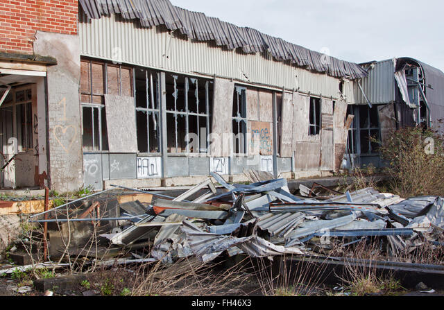 Scrap metal and rubble strewn around an abandoned factory site in UK - Stock Image