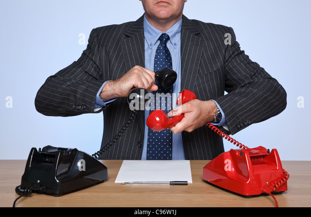 Photo of a businessman sat at a desk with two traditional telephones, one red and one black. Conference call concept. - Stock Image