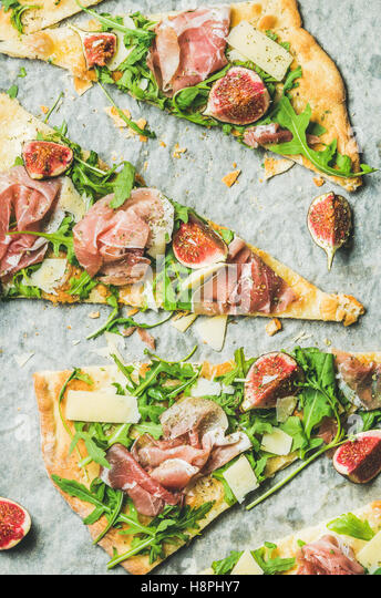 Pieces of fig, prosciutto, arugula and sage flatbread pizza - Stock Image