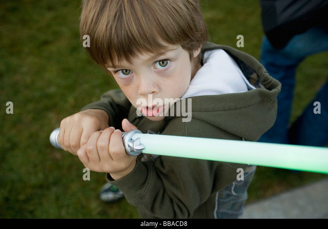 A young boy holding a toy sword - Stock-Bilder