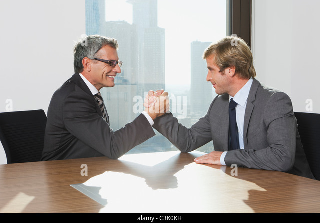 Germany, Frankfurt, Businessmen doing arm wrestling - Stock Image