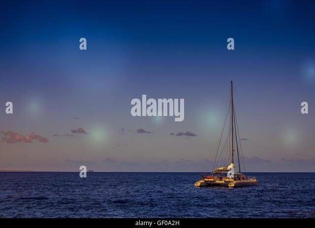 Private catamaran on the ocean at dusk, Canary Islands, Spain. Picture taken 20 April 2016. - Stock Image