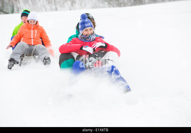 Young couples enjoying sled ride on snow covered slope - Stock Image