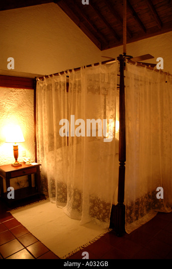 Tropics four poster bed mosquito netting Casa de Campo Resort Dominican Republic luxury suite mega resort caribbean - Stock Image