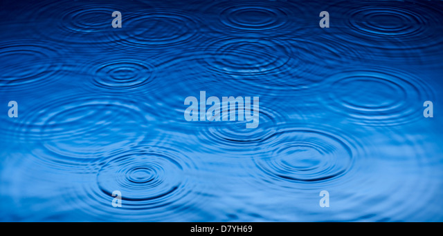 Ripples of raindrops in puddle - Stock Image