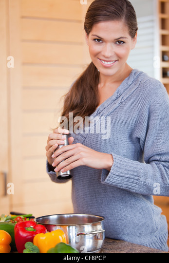 Smiling woman adding spices to her stew - Stock Image
