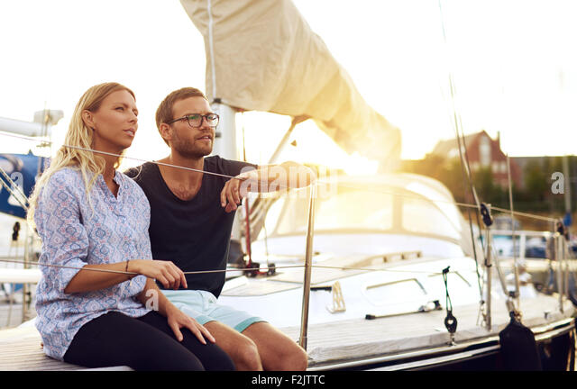 Sweet Young Lovers Sitting In Front of a Yacht and Looking Into the Distance During Sunset. - Stock Image