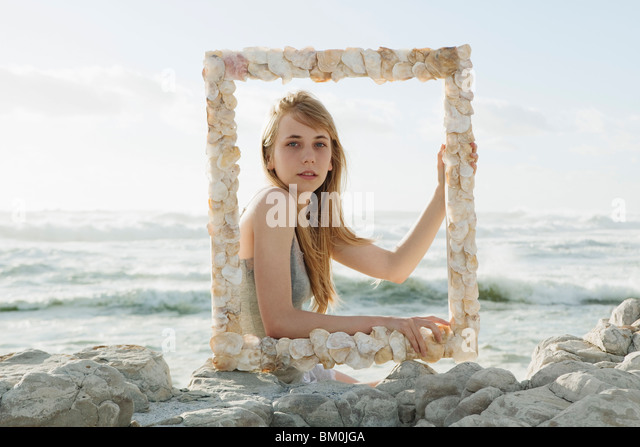 Girl holding shell picture frame - Stock Image