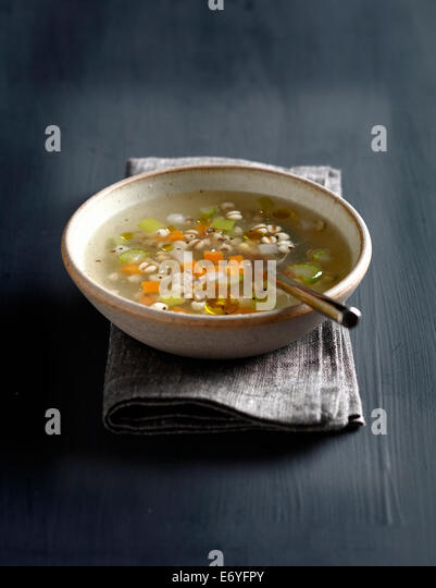 Vegetable broth with pearl barley and basil oil - Stock Image