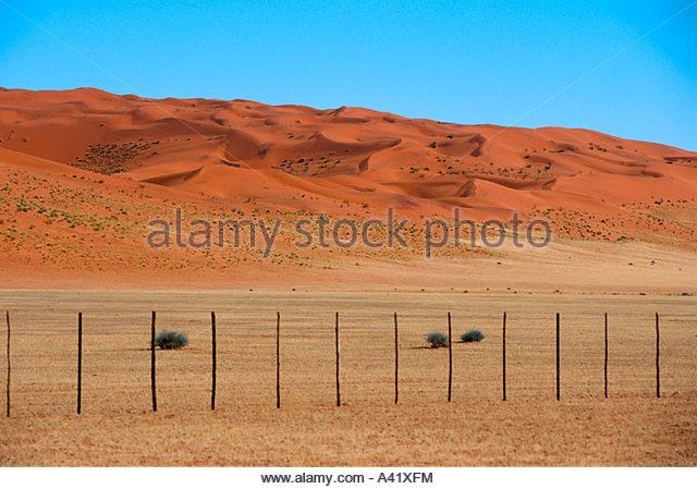 Zaun und Duenen in der Namib - Stock Image