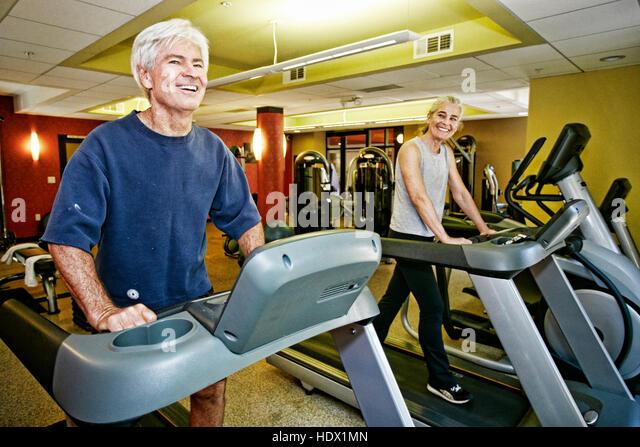 Smiling Caucasian couple on treadmills - Stock Image