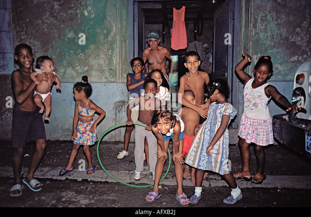 Street scene at night with children an old man and a baby in Central Havana Cuba - Stock Image