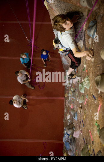 A young male teen rock climber top ropes at a rock climbing gym. - Stock Image