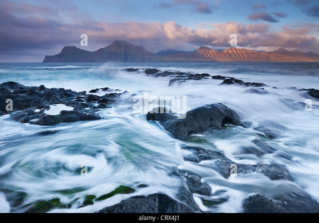 Surging waves break over the rocky shores at Gjogv on the island of Eysturoy, Faroe Islands. Spring (June) 2012. - Stock Image