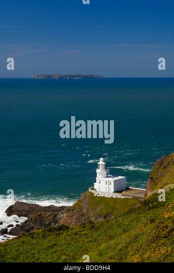 Hartland Point lighthouse on the North Devon Coast with Lundy Island on the horizon, England, United Kingdom. - Stock Image