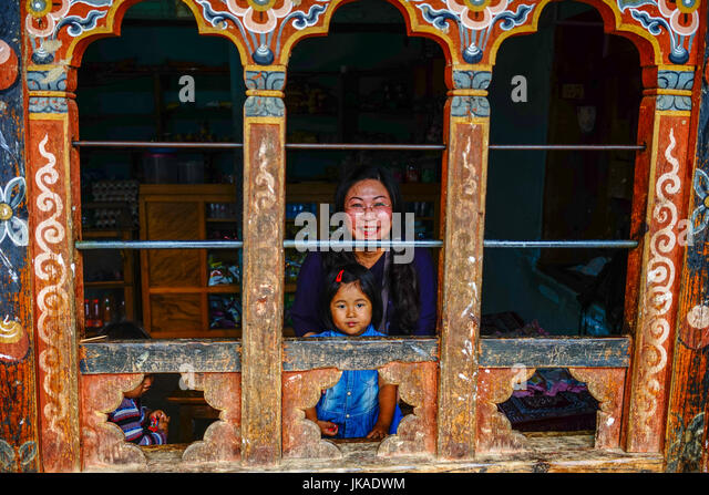 Thimphu, Bhutan - Aug 29, 2015. A Tibetan woman with her child at a traditional house in Thimphu, Bhutan. Bhutan - Stock Image