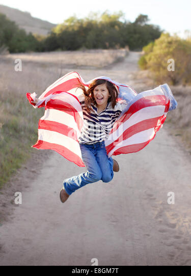 Girl jumping in the air holding American flag - Stock-Bilder