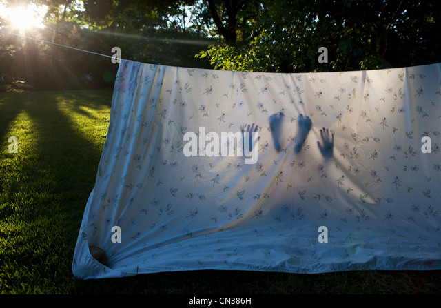 Child in homemade den made from sheet - Stock Image
