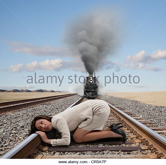 Mixed race businesswoman kneeling on railroad tracks - Stock Image