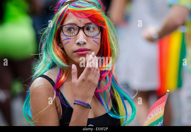 NEW YORK CITY, USA - JUNE 28, 2015: Young woman dressed in colorful wig looks at the festivities of the annual Pride - Stock-Bilder