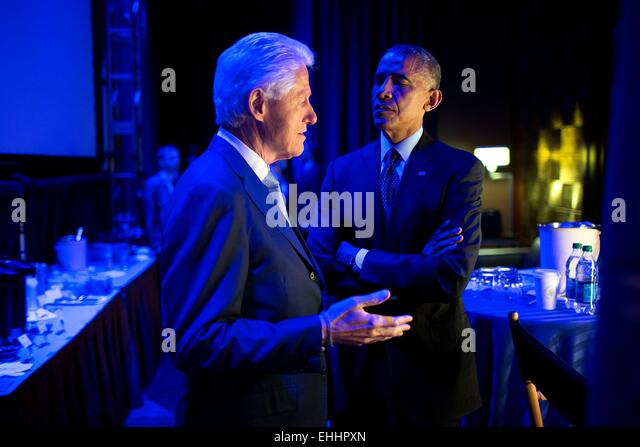 US President Barack Obama speaks with former President Bill Clinton backstage prior to delivering remarks during - Stock Image