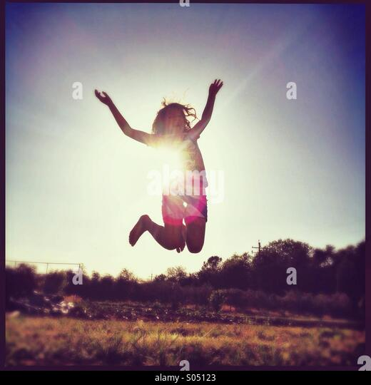 Girl jumping with sun at her back. - Stock Image