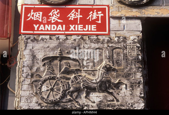 Detail of stone carving depicting rider on a horse and chariot and sign for Yandaixie Jie Beijing - Stock Image