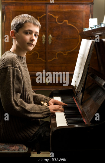 portrait of a young man playing the piano - Stock-Bilder