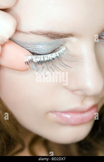 Young woman applying fake eyelashes - Stock Image