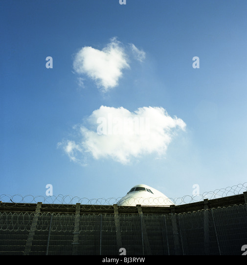 The cockpit section of a Boeing 747 jumbo jet is perceived peering over the barbed-wire perimeter fence at Heathrow - Stock Image