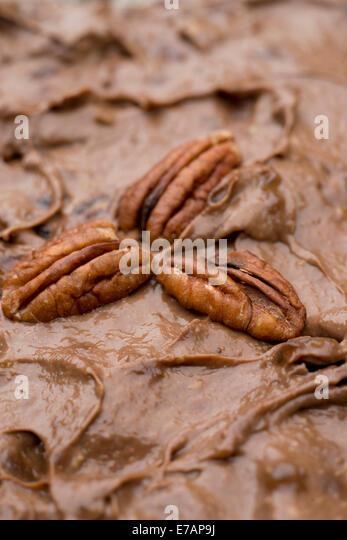 Vegan chocolate brownie with pecan nut decoration. - Stock Image