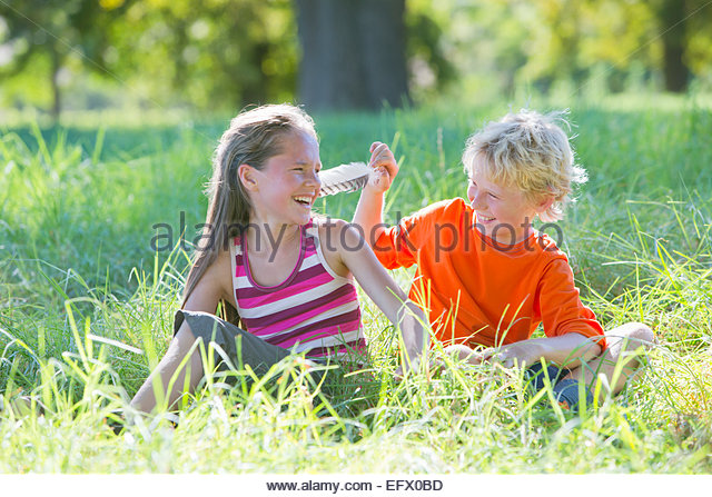 Young boy tickling young girl with feather, sitting in treelined field - Stock Image