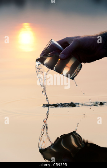 Pouring water from a glass into a still lake at sunrise in India. Silhouette - Stock Image
