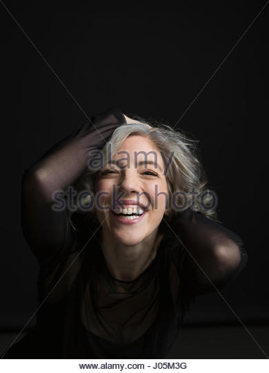 Portrait enthusiastic woman laughing with hands in hair against black background - Stock Image