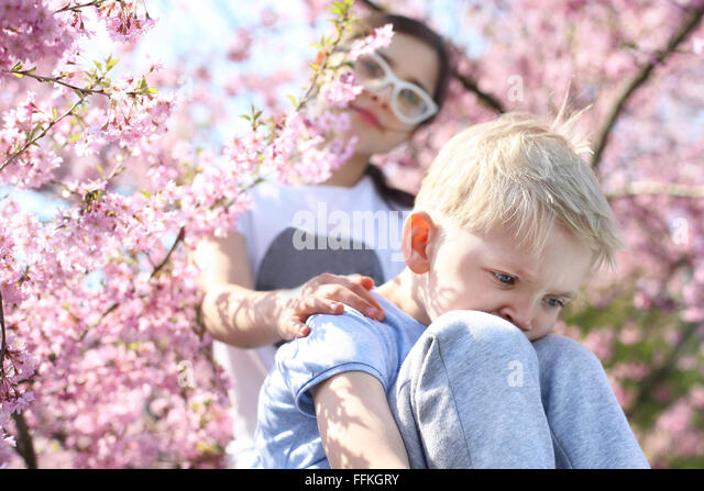Keep your head up, it will be well!. Children sitting under a blooming tree, sister comforted by his brother - Stock Image