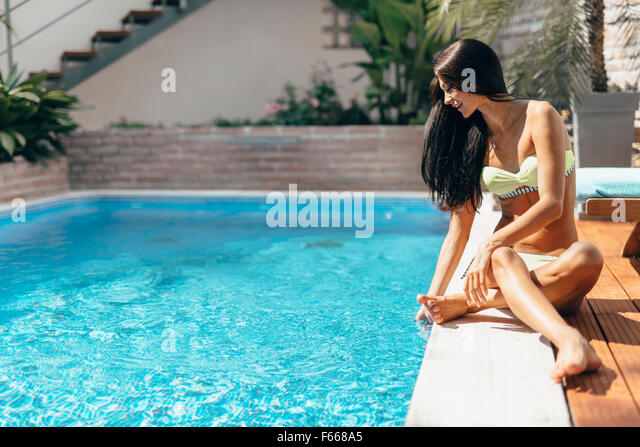 Young beautiful woman on the side of the pool playing with water displaying sensuality - Stock Image